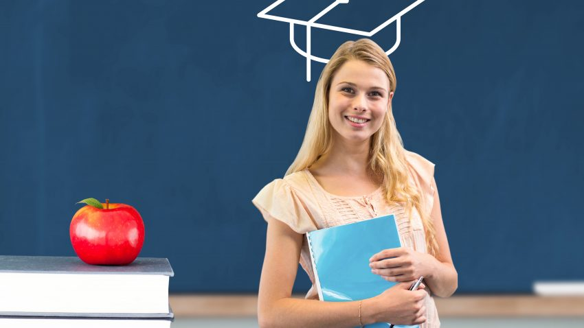 Happy teenage girl holding book with mortarboard head smiling at camera in the classroom